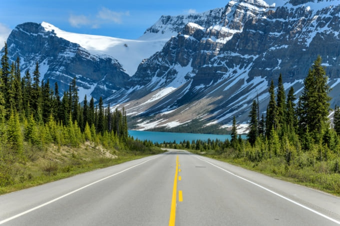 Icefields Parkway at Bow Lake - A Spring evening view of Icefields Parkway extending towards Bow Lake, with BowCrow Peak, Crowfoot Glacier and Crowfoot Mountain rising high behind, Banff National Park, AB, Canada.