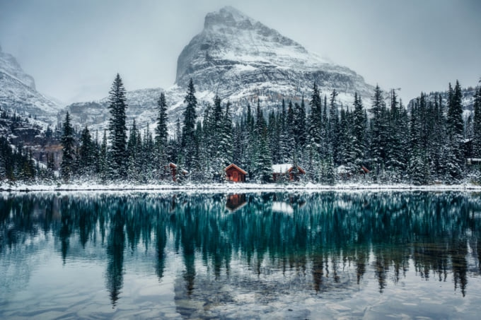 Wooden lodge in pine forest with heavy snow reflection on Lake O'hara at Yoho national park